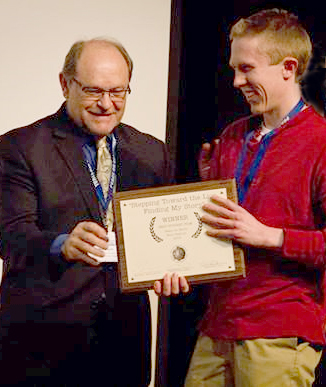 Photo of John Lyden accepting Best Student Film Peace on Earth Film Festival